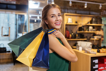 happy young woman with shopping bags at shoestore