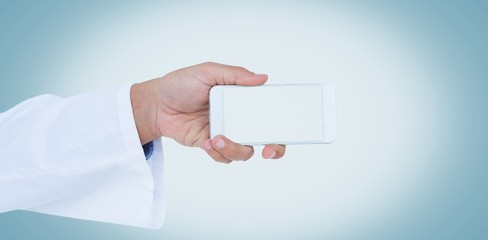 Male doctor holding smart phone with blank screen