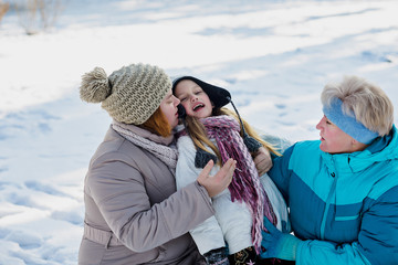 Mother, daughter, grandmother play in snow