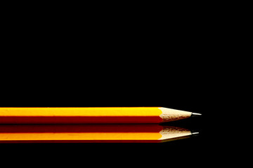 A wooden sharp pencil with an eraser. Isolated on black..