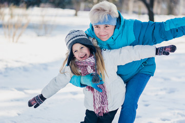 Active grandmother and little girl play in snow in winter sunny day