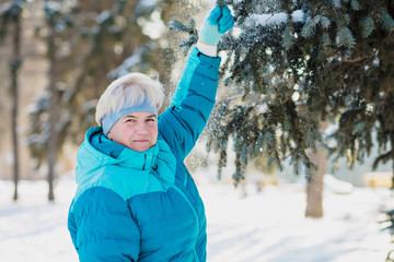 Mature active blonde woman in blue sporty jacket in winter park