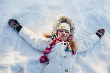 Little girl lays on the snow. Games in winter time. Top view