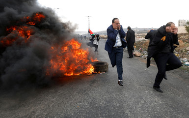 Palestinian lawyers run during clashes with Israeli troops at a protest near the Jewish settlement of Beit El, near the West Bank city of Ramallah