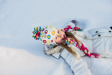 Happy little girl lays on the snow. Winter leisure