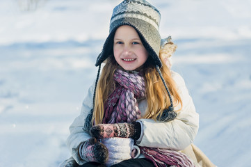 Little girl holds hot cup of tea outdoor. Winter time