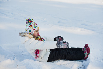 little girl sits on the snow