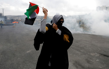 Palestinian lawyer reacts to tear gas fired by Israeli troops during clashes at a protest near the Jewish settlement of Beit El, near the West Bank city of Ramallah