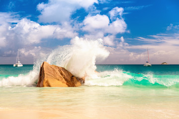 Big sea wave breaking on the shore rock with stunning blue ocean water on background