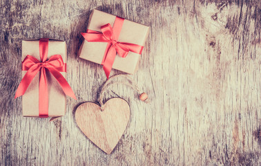 Gift box with  bow and wooden heart on an old wooden table. Copy space. Valentine's Day.