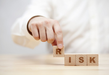 Hand and word Risk made with wooden building blocks