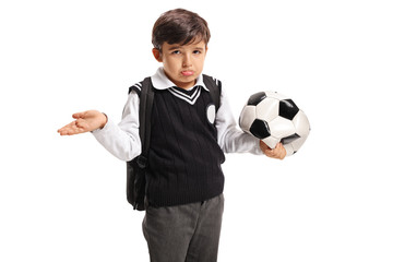 Disappointed little schoolboy holding a deflated football
