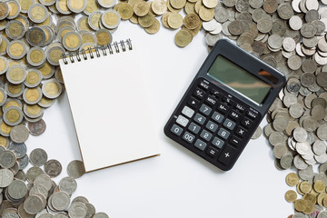 Business finance concept notebook paper and calculator on coins background