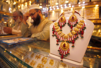 A gold necklace is seen on the counter as shopkeepers wait for customers at a jewelry shop in Peshawar