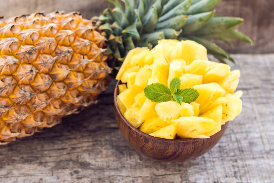 Pineapple slices and pineapple shelled Asian-style on the old wooden background. Tropical fruit concept