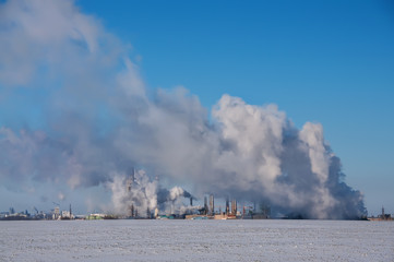 Steam wallows with the production, heat complex in the winter. A production complex standing in the middle of a snow-covered field. Industrial buildings and smoking pipes