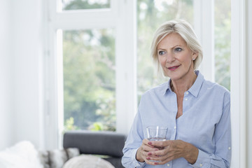 Portrait of smiling senior woman with glass of water in the living room