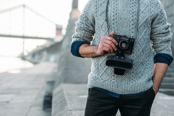 cropped shot of man in stylish sweater with vintage film camera outdoors