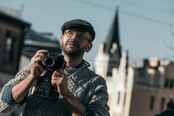 handsome adult man with vintage film camera in old european town