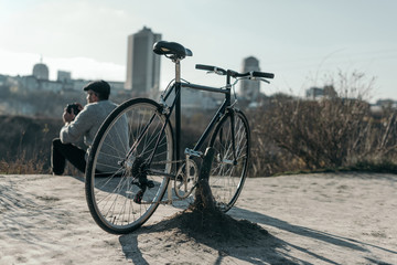 adult man with bicycle sitting on rural road and looking at city