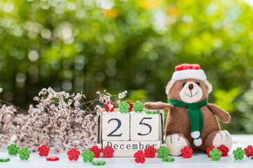 Wooden calendar show date of December 25 , Christmas day .There are dry flower and mini bear in the background
