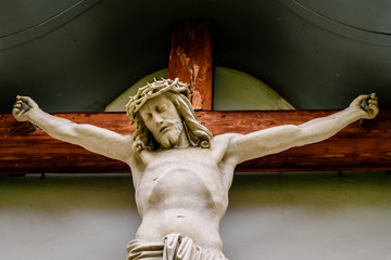 a Jesus statue on a cross carved from wood and painted