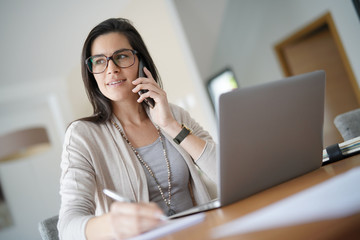 Businesswoman working from home talking on phone