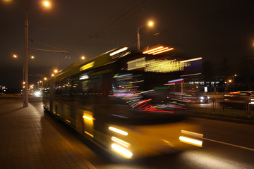 The motion of a blurred bus on the avenue in the evening
