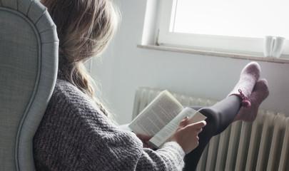 Junge Frau entspannt im Sessel und liest ein Buch