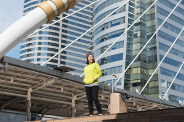 Happy female tourist with suitcase while in city building, Travel concept