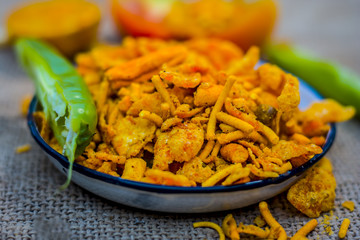 Close up Indian snack mix chevdo in a plate with green chillies.