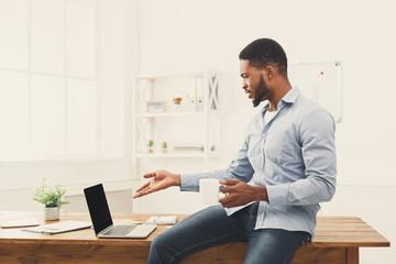 Surprised balck businessman looking at laptop
