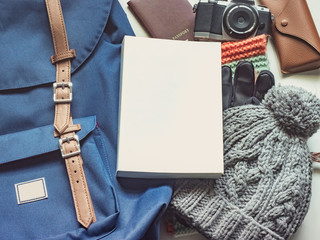 long holiday travel flat lay concept from winter cloth item and blue backpack with passport , retro camera , sunglasses and book put on isolated white background