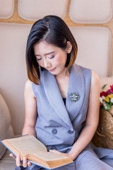 beautiful asian woman in formal dress reading book on armchait portrait photo
