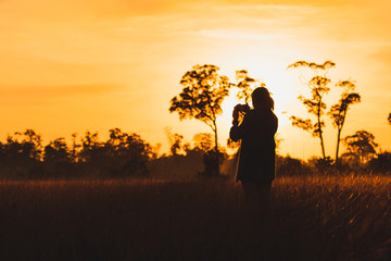 Silhouette of female photographer  taking picture of meadow at sunrise