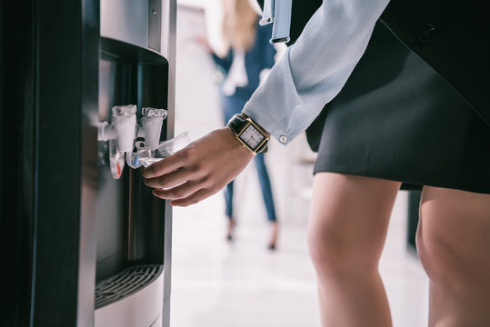 cropped shot of businesswoman pouring water from dispenser