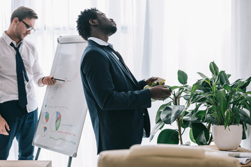 sleepy african american manager spraying plant with water at office while his colleague making presentation