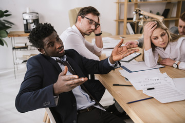 overworked buisness partners having conversation at office
