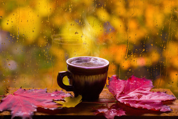 Cup of hot coffee on a rainy autumn window