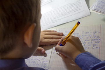 Close-up of boy hand with pencil writing english words by hand on traditional white notepad paper.