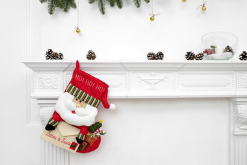 A close picture of beautifully decorated Santa Christmas socks with ho! ho! ho! word hanging on a fireplace waiting for presents.