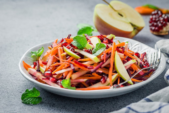 Raw carrot beetroot apple salad with ginger lime dressing on stone background. Selective focus, copy space.