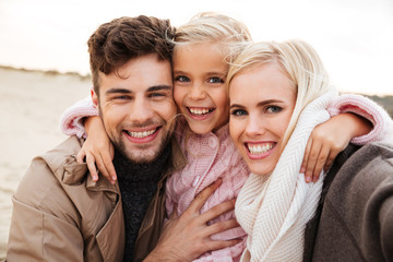 Portrait of a cheerful family with a little daughter
