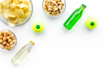 Snacks for watching TV. Crisps, popcorn, rusks near drinks on white background top view copyspace