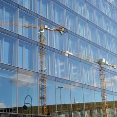 Spiegelung eines Baukranes in der Glasfassade eines Bürogebäudes in Berlin