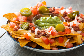 Mexican nachos with beef, guacamole, cheese sauce, peppers, tomato and onion in plate on wooden table