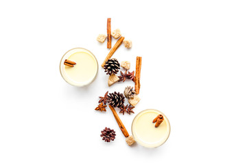 Winter attributes. Glasses of classic eggnog with spices on white background top view copyspace
