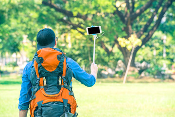 Tourist man with a backpack holding a phone with a stick and taking a selfie in the nature. Digital nomad and travel tourism hike technology concept