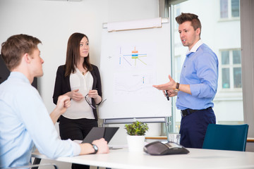 Male Professional Explaining Chart To Coworkers In Office