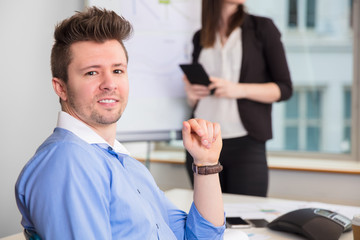 Confident Businessman Smiling While Colleague Standing At Office